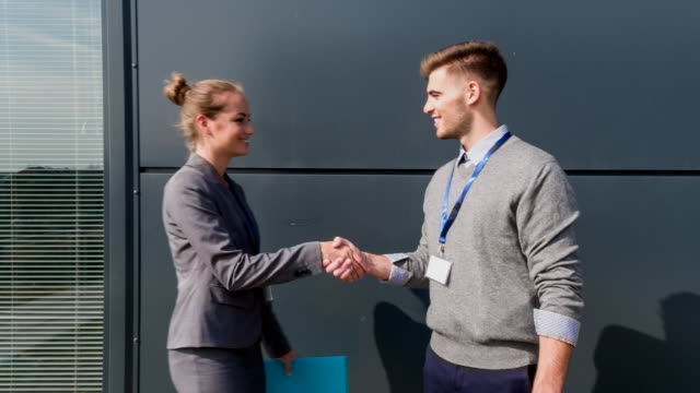 MS businesspeople meeting outdoors shaking hands