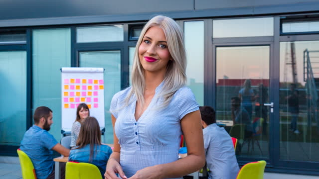 CU businesspeople meeting outdoors, woman looking at camera
