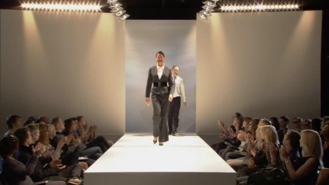 vídeos de stock e filmes b-roll de ws businesspeople modeling on catwalk while audience applauds / london, england, uk - desfile de moda