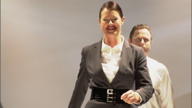 ms zo ws businesspeople modeling on catwalk while audience applauds / london, england, uk - この撮影のクリップをもっと見る 1064点の映像素材/bロール