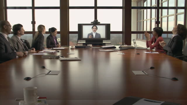 ms businesspeople on video conference call in conference/ people clapping an high fiving with boss on monitor gives good news/ montclair, new jersey - ビデオ点の映像素材/bロール