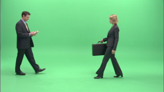 ws, businesspeople passing bundle of money and briefcase to each other in studio - aktentasche stock-videos und b-roll-filmmaterial