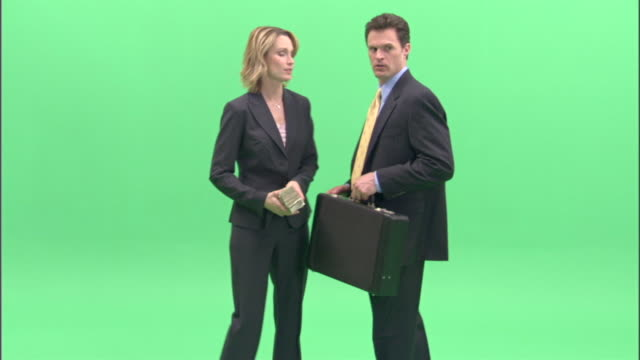 ms, businesspeople passing bundle of money and briefcase to each other in studio - aktentasche stock-videos und b-roll-filmmaterial