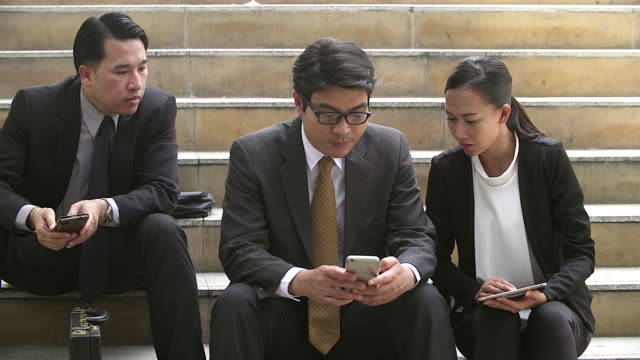 Businesspeople relaxing by playing with mobile phone.