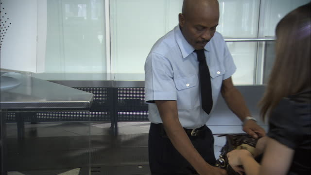 ms pan zi businesspeople retrieving luggage from x-ray machine conveyor belt at airport security checkpoint/ munich, germany - reisegepäck stock-videos und b-roll-filmmaterial