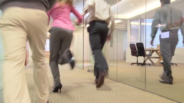 Businesspeople running down hallway