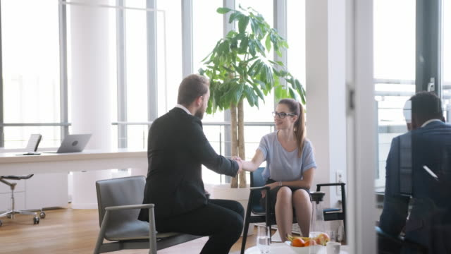 businesspeople shaking hands in modern office lobby - lobby stock videos & royalty-free footage