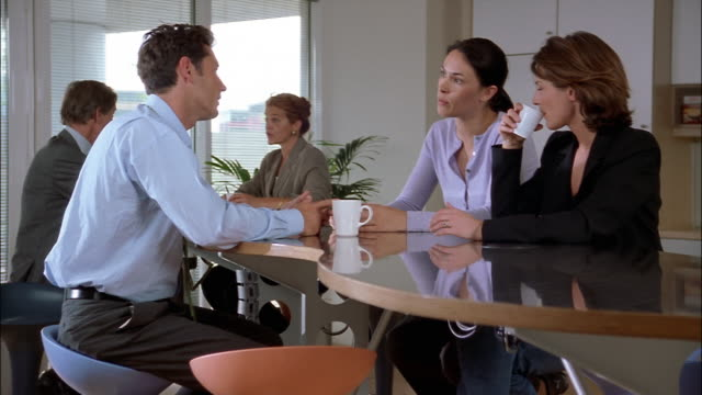 Businesspeople sit at a high cafeteria table in a coffee shop.