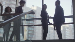 Businesspeople Talking on Landing of Office Building Staircase