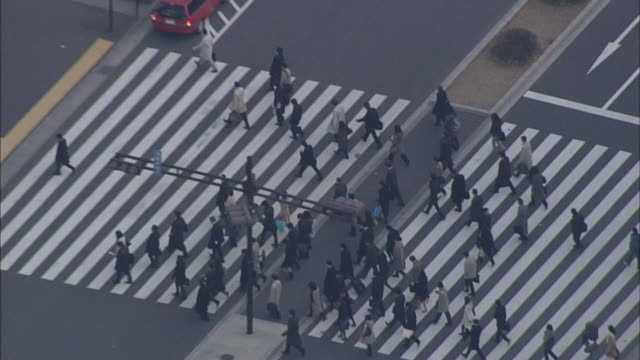 Businesspeople use the Marunouchi side crosswalk at Tokyo Station.