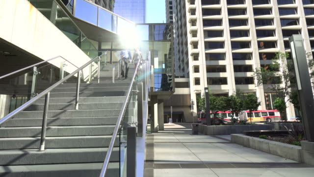 businesspeople walk down stairs from an office building - moving down stock videos and b-roll footage