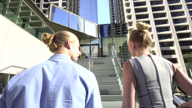 businesspeople walk up stairs to an office building - gradino video stock e b–roll