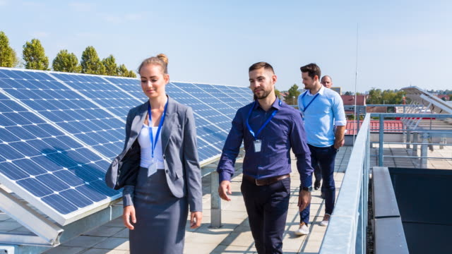 vídeos y material grabado en eventos de stock de ms businesspeople walking between solar panels - recursos sostenibles
