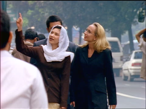 3 businesspeople walking down street in Jakarta / man on cellular phone as Muslim woman points