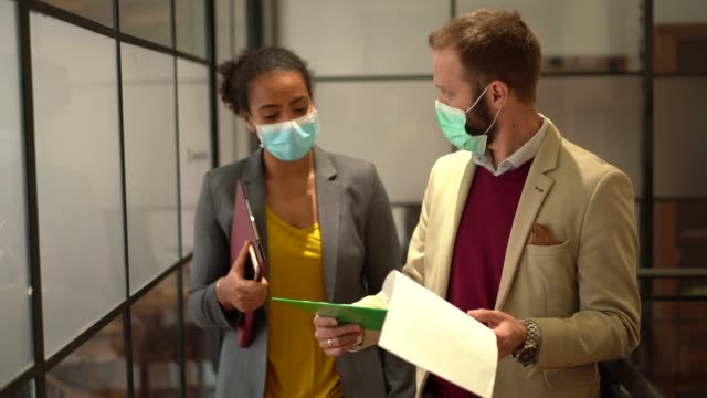 businesspeople wearing face masks at work during covid-19 pandemic - health and safety stock videos & royalty-free footage