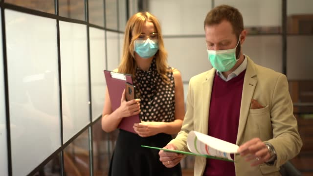 businesspeople wearing face masks at work during covid-19 pandemic - epidemia video stock e b–roll