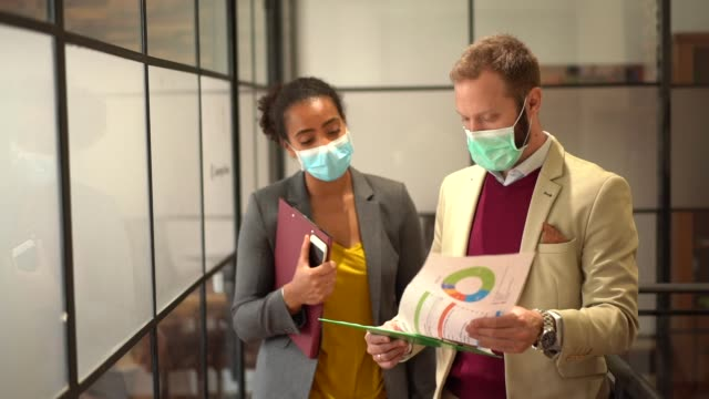 businesspeople wearing face masks at work during covid-19 pandemic - place of work stock videos & royalty-free footage