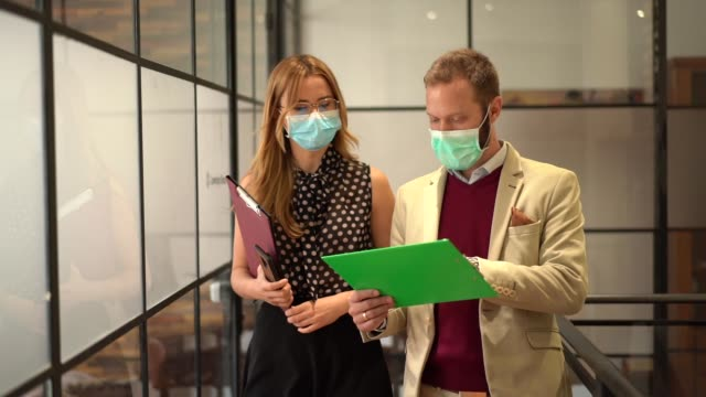 businesspeople wearing face masks at work during covid-19 pandemic - collega d'ufficio video stock e b–roll