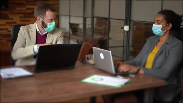 businesspeople with face masks in the office during covid-19 pandemic - meeting stock videos & royalty-free footage