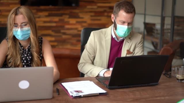 businesspeople with face masks in the office during covid-19 pandemic - pollution mask stock videos & royalty-free footage
