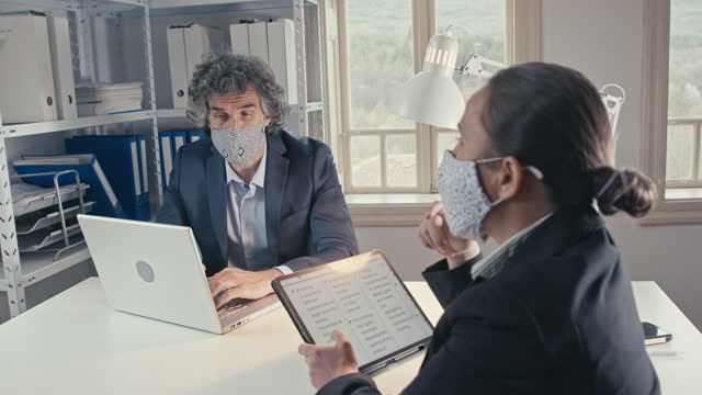 businesspeople working in office while covid-19 pandemic, wearing protective face masks to flatten the curve. sustainable development goals-working in paper free office space, brainstorming, teamwork. - brainstorming stock videos & royalty-free footage