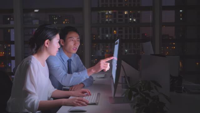 ms businesspeople working late at night - 指差す点の映像素材/bロール