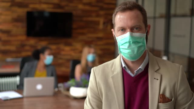 businesspeople working with face masks in the office during covid-19 pandemic - health and safety stock videos & royalty-free footage