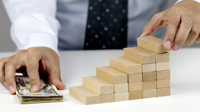 テーブルの上に紙幣を置き、成長を示すために木製のブロックを置くビジネスパーソン - 天地創造点の映像素材/bロール