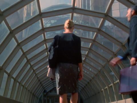 businesspersons greeting each other in pedestrian skybridge - überdachte brücke brücke stock-videos und b-roll-filmmaterial