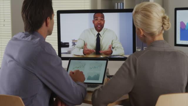 vidéos et rushes de businessteam listening to manager in a video conference - tenue d'affaires formelle