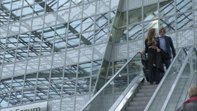 stockvideo's en b-roll-footage met la ws businesswoman and businessman descending escalator outside modern airport / munich, germany - münchen vliegveld