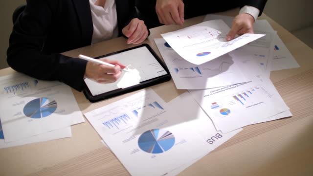 vídeos y material grabado en eventos de stock de empresaria y empresario tienen conversación con documento gráfico en la oficina - ciencia y tecnología