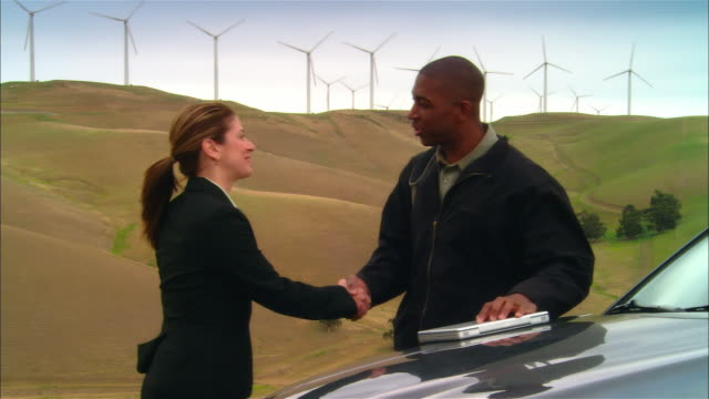 MS DS Businesswoman and businessman shaking hands near wind turbines on hill, then woman enters SUV / Livermore, California, USA