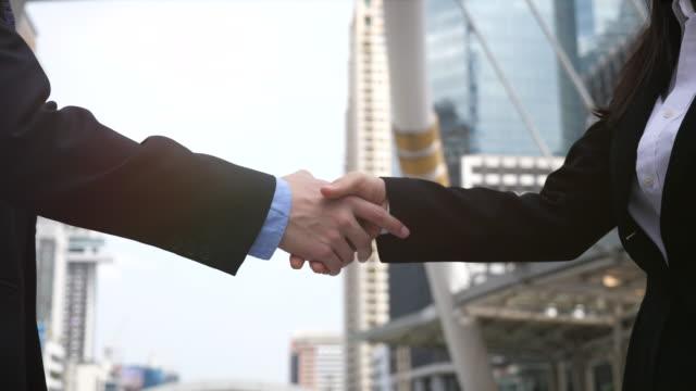 vídeos de stock, filmes e b-roll de mulher de negócios e homem de negócios que agitam mãos - cliente