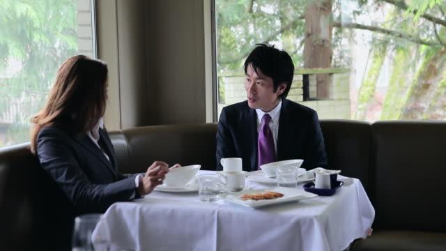 ms businesswoman and businessman sitting having meeting at table in restaurant/washington, usa - hel kostym bildbanksvideor och videomaterial från bakom kulisserna