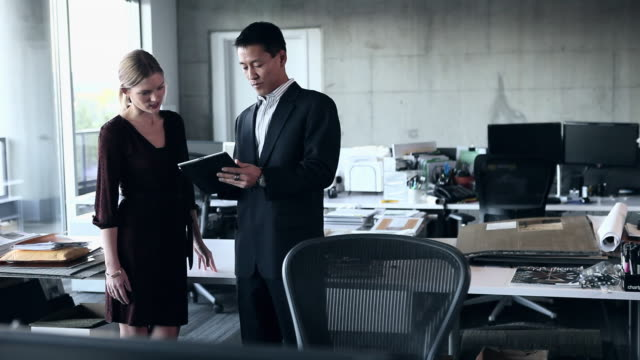 WS PAN Businesswoman and businessman standing in empty office looking at digital tablet/Washington, USA