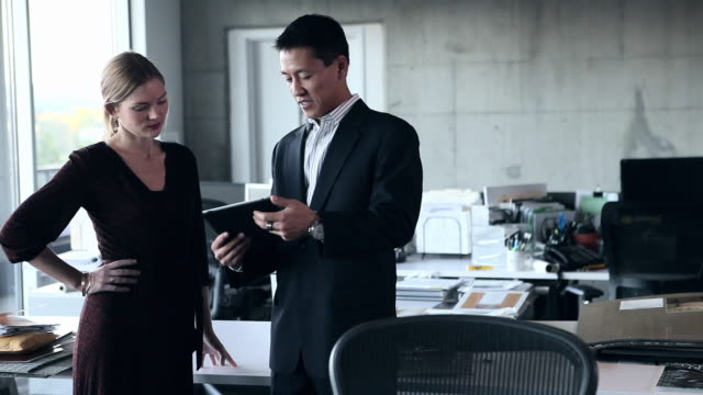 MS PAN Businesswoman and businessman standing in empty office looking at digital tablet/Washington, USA