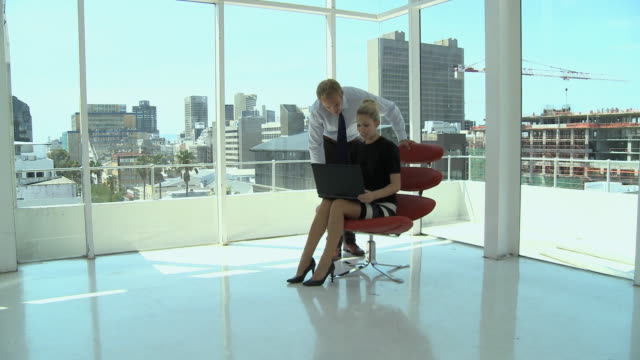 vídeos de stock e filmes b-roll de ws pan businesswoman and businessman using laptop in office, cape town, south africa - camisa e gravata