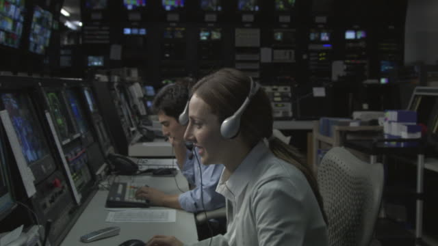 ms businesswoman and businessmen working on computers in television studio control room / culver city, california, usa - female with group of males stock videos and b-roll footage