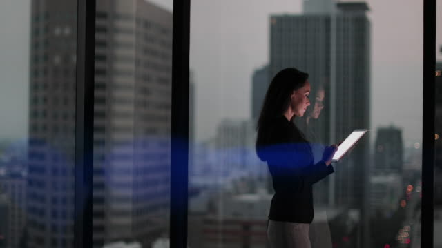 businesswoman and reflection working late using digital tablet with bokeh effect - businesswoman stock videos & royalty-free footage