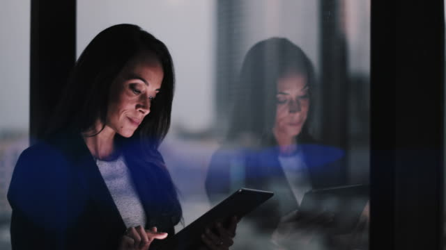 Businesswoman and reflection working late using digital tablet with bokeh effect