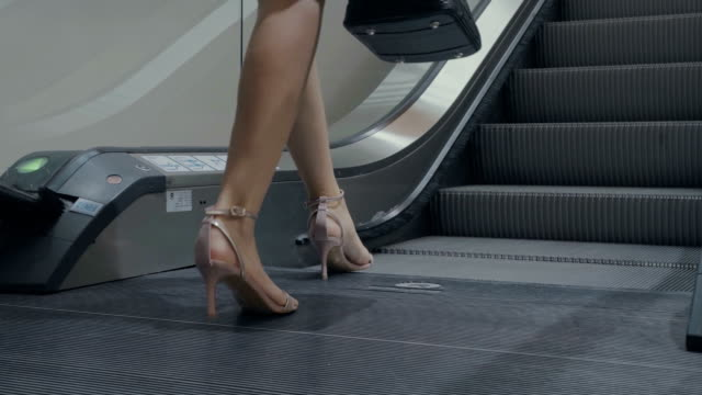 Businesswoman ascending escalator in office building