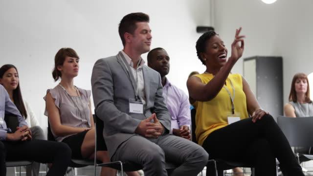 businesswoman asking a question at a conference - namensschild etikett stock-videos und b-roll-filmmaterial