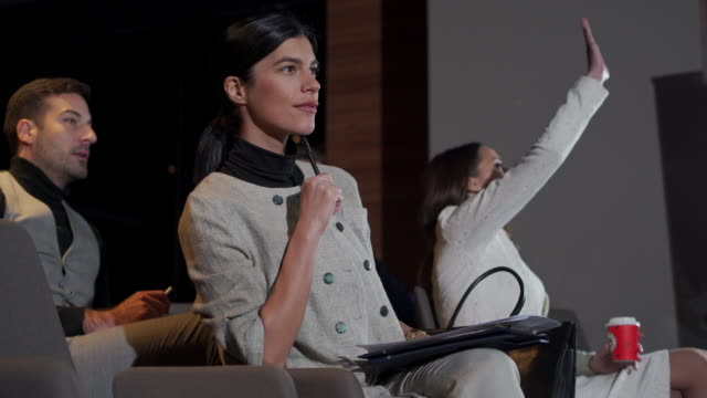 vidéos et rushes de femme d'affaires posant une question pendant une présentation d'affaires - congrès d'affaires