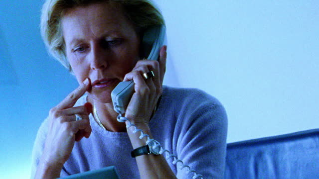 blue selective focus canted businesswoman at desk in front of laptop talking on telephone - only mid adult women stock videos & royalty-free footage