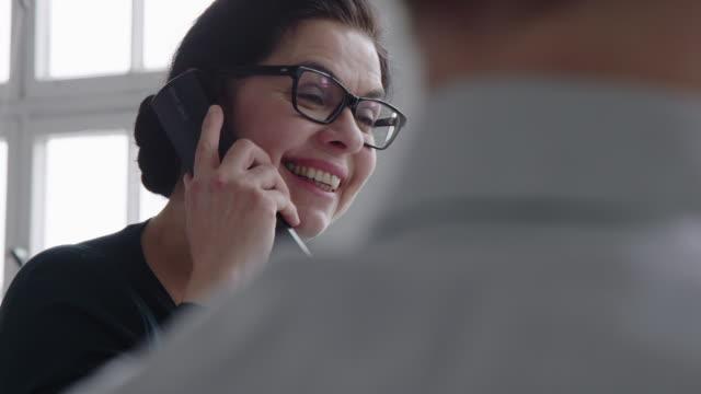 vídeos y material grabado en eventos de stock de mujer de negocios en su lugar de trabajo hablando por teléfono fijo - teléfono con cable
