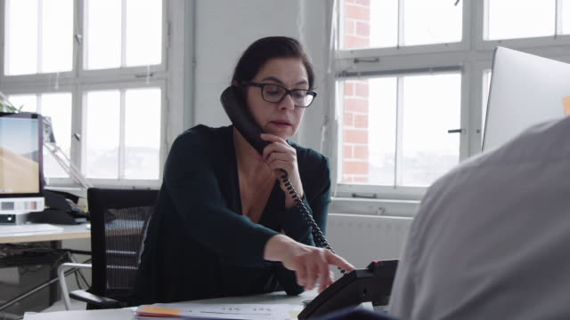 businesswoman busy working at her desk - landline phone stock videos & royalty-free footage