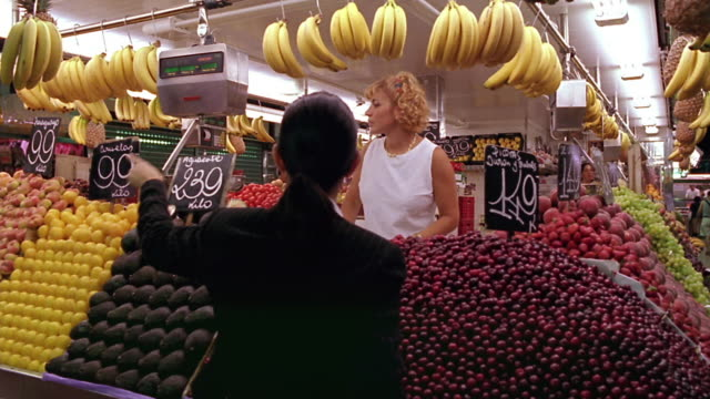 REAR VIEW businesswoman buying fruit / woman behind counter weighs bananas / Barcelona, Spain