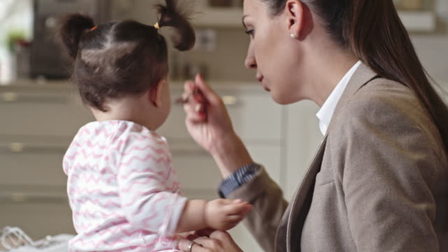 businesswoman caring for baby daughter - haarzopf stock-videos und b-roll-filmmaterial