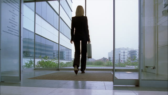 A businesswoman carrying a briefcase exits the lobby of an office building.